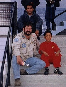 Jesus Peralta, latest ARTI member as a little Boy in Ilo, Peru. He was wearing a 'tiny' version of the National Fire Dept of Peru (I later became a Captain, in the National Fire Dept of Peru.)   Chico Peralta, Jesus fatheris sitting behind us. Doug Copp.
